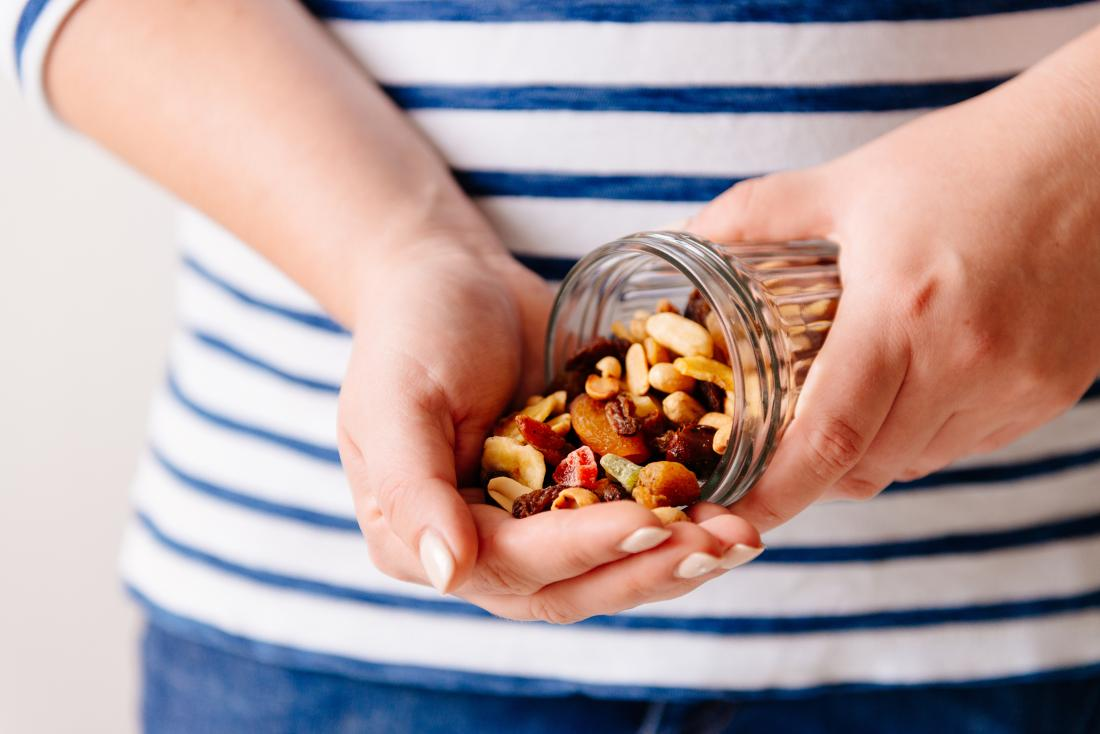woman-pouring-nuts-and-dried-fruit-into-hand